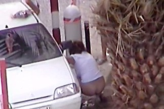 Mature and absolutely hot woman pissing in front of a car