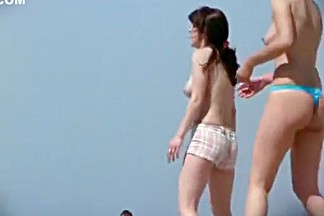 Topless girls playing beach volley ball